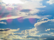 Heavenly clouds wallpaper. White clouds, blue sky, sun shining and a celestial light. This image, can be associated to the idealization of paradise Stock Photography