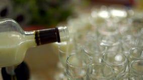 Paradiso alcolico La mano del ` s dell'uomo versa una bevanda alcolica Sulla tavola, molti piatti in cui versano una bevanda archivi video