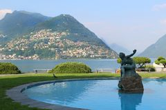 Paradiso, Lugano, Switzerland. View of mountains in Paradiso, Lake Lugano, Switzerland with fountain in the front Royalty Free Stock Images