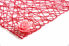 Paraffin rose. On a red rope mesh Stock Photo
