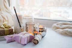 Paraffin wax candles and one tealight in a glass candle holder and aroma stick, romantic gift boxes, standing on a windowsill. Early morning, concept of romance royalty free stock photo