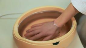 Paraffinterapi för händer i kosmetisk klinik arkivfilmer