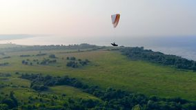 Parafoil is drifting above the fields and water