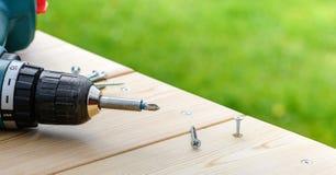 Parafuse o parafusamento em uma placa de madeira pela chave de fenda elétrica Imagem de Stock