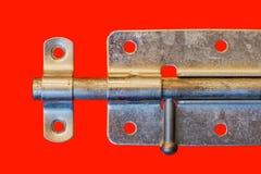 Parafuso de porta de aço, isolado em um fundo vermelho fotografia de stock royalty free