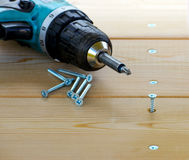 Parafuso e broca elétrica em uma placa de madeira Fotografia de Stock