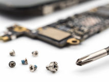 Parafuso e chave de fenda com componentes borrados do smartphone foto de stock royalty free
