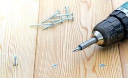 Parafuso e chave de fenda elétrica em uma placa de madeira Foto de Stock Royalty Free