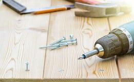 Parafuso e chave de fenda elétrica em uma placa de madeira Fotografia de Stock