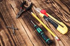 Parafuso, faca da chave de fenda e dos artigos de papelaria e pinças do lápis imagem de stock royalty free