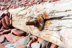 Parafuso oxidado velho em madeira rachada em rochas Fotografia de Stock Royalty Free