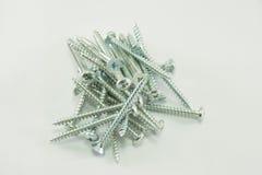 Parafusos de prata posicionados em um fundo branco isolado Fotografia de Stock