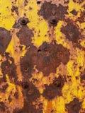 Parafusos do ferro do fundo na parede oxidada do metal com descascamento da pintura amarela imagem de stock royalty free