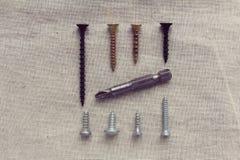 Parafusos e bocados para a chave de fenda apresentados no tecido de algodão fotografia de stock royalty free