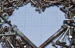 Parafusos e porcas no papel do milímetro Coração dado forma Espaço livre Foto de Stock Royalty Free