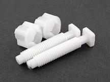 Parafusos e porcas plásticos brancos do toalete em um fundo escuro Imagens de Stock Royalty Free