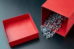 Parafusos folheados a níquel novos em um recipiente vermelho Acessórios para mecânicos em uma tabela de madeira fotos de stock royalty free