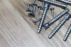 Parafusos longos e curtos, afiados e sem corte-aguçados em uma tabela de madeira fotografia de stock