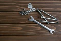 Parafusos longos e porcas do cromo que encontram-se em pranchas de madeira ao lado da chave de a?o fotografia de stock royalty free