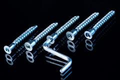 Parafusos poderosos e chave para o reparo do equipamento em um fundo preto fotografia de stock