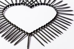 Parafusos pretos apresentados na forma de um coração em um fundo branco imagem de stock royalty free