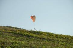 paraglide飞行剪影在天空的与在日出光的云彩  乌克兰喀尔巴阡山脉的谷 免版税图库摄影