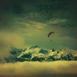 Paraglide επάνω από τις χιονοσκεπείς αιχμές Εκλεκτής ποιότητας χρώματα Στοκ Εικόνες