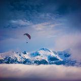 Paraglide above the snow-capped peaks. Paraglide silhouette in a light of sunrise above the snow-capped peaks of winter mountains Royalty Free Stock Image