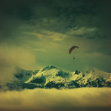Paraglide above the snow-capped peaks. Vintage colors Stock Images