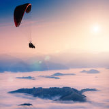 Paraglide in a morning sky. Paraglide silhouette over misty mountain valley Royalty Free Stock Photos