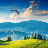Paraglide over Laseshina valley. Paraglide silhouette flying over Carpathian misty mountains in a light of sunset Stock Images