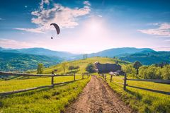 Paraglide silhouette against sky. Flying over the carpathian mountain village. Meadow, covered with fresh spring grass in a bright sun light Stock Images
