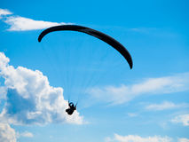 Paraglide silhouette with blue sky and white clouds. Dark paraglide silhouette on background of blue summer sky and white clouds. Adrenalin sport theme Royalty Free Stock Image