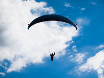 Paraglide silhouette with blue sky and white clouds. Dark paraglide silhouette on background of blue summer sky and white clouds. Adrenalin sport theme Stock Photo