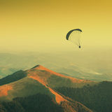 Paraglide silhouette in a Carpathian mountains. Vintage. Paraglide silhouette in a light of sunrise above the misty valley. Warm vintage colors Stock Photography