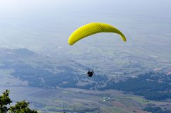Paraglide silhouette flying over misty mountain Stock Images