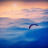 Paraglide silhouette in a light of sunrise. Vintage colors. Paraglide silhouette in a light of sunrise above the misty Crimea valley. Vintage colors Royalty Free Stock Images
