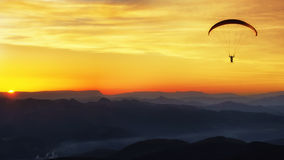 Paraglide silhouette over mountains at sunset. Paraglide silhouette over mountains at the sunset Stock Photo