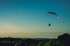Paraglide silhouettes flying on sky. Paraglide silhouettes flying on the sky. High contrast photo before the sunset Royalty Free Stock Image