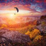 Paraglide in a sky above the misty valley. Wonderful bright colorful sunrise with beautiful red clouds Stock Photos