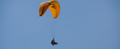 Paraglide tandem with yellow parachute in the blue Stock Image