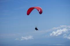 Paraglider över österrikiska fjällängar Arkivbild