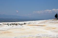 Paraglider över de Pamukkale travertineterrasserna, Turkiet Fotografering för Bildbyråer