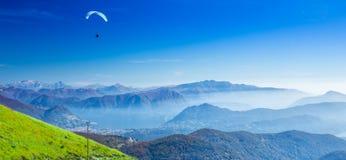 Paraglider över den Lugano staden, det San Salvatore berget och Lugano sjön som ses från Monte Lema, kanton Ticino, Schweiz arkivfoto