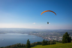 Paraglider över den Zug staden, Zugerseen och de schweiziska fjällängarna Arkivfoto