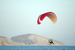 Paraglider. Red hang glider flying above sea Stock Photo