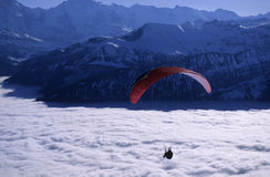 Paraglider. Above clouds, in the background the hills and mountains of Bernese highlands Stock Photography