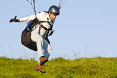 Paraglider. A closeup view from a paraglider starting to take off from a cliff with generic vegetation behind. Land-based paragliding practice during training Stock Photography