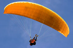 Paraglider. Orange winged paraglider flies in the blue sky Royalty Free Stock Photography