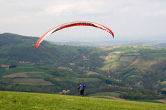 Paraglider. With red glider taking off Royalty Free Stock Photos